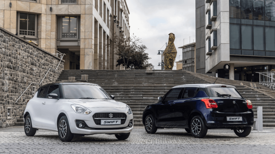 Two suzuki swifts parked in front of stairs